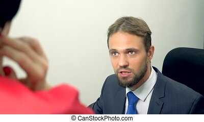 office flirt. man close-up talking to a brunette in red clothes. flirting with his colleague.