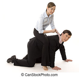 A female businesswoman sits astride a male colleague