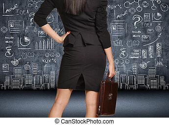 Office girl in skirt with a briefcase looking at figure drawn chalk on the wall