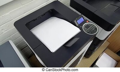 Office laser jet printer printing a lot of pages paper of A4 or letter size in a storehouse - 19th of September 2019