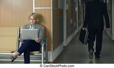 Office Lobby - Woman working at the computer in the lobby of...