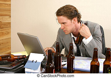 Business man at desk with empty beer bottles.