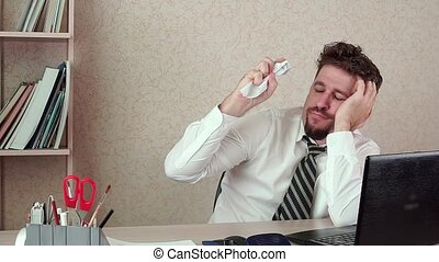 Office Manager bearded man, bored at work, throws a crumpled sheet of paper