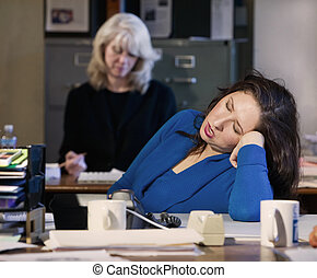 Office Nap - Hispanic woman sleeps at her office desk
