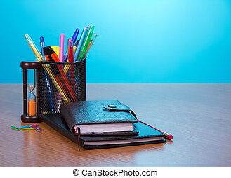 Notepad, organizer, a support with office supply and the calculator on a table