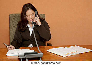 Office Phone - A woman sitting at her desk talking on the...