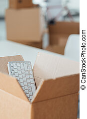 Office relocation - Open cardboard box and empty office on...