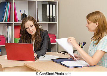Office Specialist intensely looking for information on a laptop, sitting next to the client