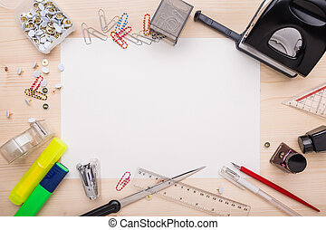 Office supplies and a white piece of paper in the center