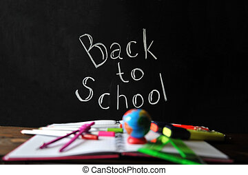Office supplies spread out on a notebook lying on a table on the background of a chalk lettering time to school