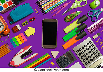 office supplies surrounding a mobile phone