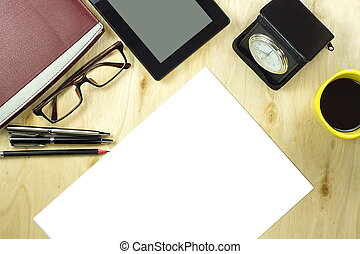 Office table desk top view with tablet PC,a cup of coffee, pen, pencil, glasses, clock, book and blank paper on wooden background.