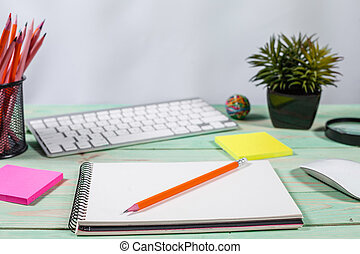 Office table desk with set of colorful supplies, flower on blue background