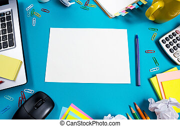 Office table desk with set of colorful supplies, white blank note pad, cup, pen, pc, crumpled paper, flower on blue background. Top view and copy space for text