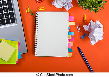 Office table desk with set of colorful supplies, white blank note pad, cup, pen, pc, crumpled paper, flower on red background. Top view and copy space for text