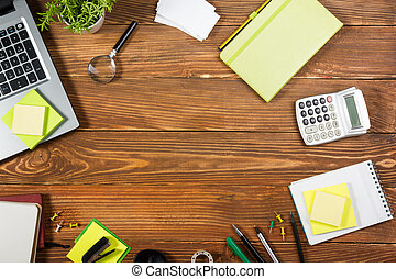 Office table desk with set of colorful supplies, white blank note pad, cup, pen, pc, crumpled paper, flower on wooden background. Top view and copy space for ad text