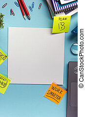 Office table desk with supplies, blank note pad, cup, pen, pc, crumpled paper, flower on blue background. Top view