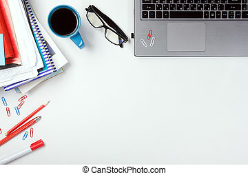 Office table desk with supplies, blank note pad, cup, pen, pc, crumpled paper, flower on white background. Top view