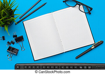 Office table desk with supplies on blue background, Top view and copy space for text