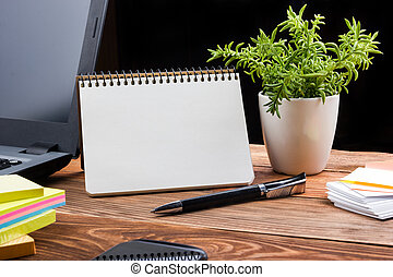 Office table desk with supplies, white blank note pad, cup, pen, pc, crumpled paper, flower on wooden background. Top view