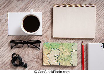Office table with a coffee cup, a blank notepad and supplies