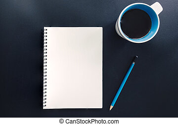 Office table with blank notepad, pencil, and cup of coffee.