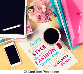 Office table with fashion magazines, digital tablet,...