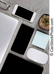 Office table with laptop computer, digital tablet, pen, smartphone, mouse, eyeglasses and coffee on white wood background. Desktop office mockup concept.