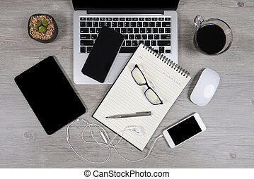Office table with laptop computer, notebook, digital tablet, pen, smartphone, mouse, eyeglasses and coffee on white wood background. Desktop office mockup concept.