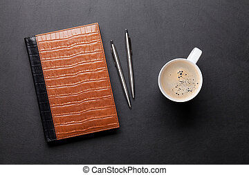Office table with notepad, coffee, pen and pencil