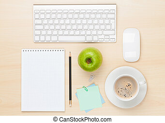 Office table with notepad, computer and coffee cup. View...