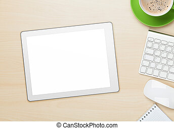 Office table with tablet, notepad, computer and coffee cup