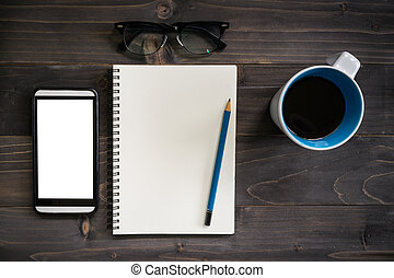 Office wood table with blank notepad, pencil, glasses, phone and white cup of coffee.