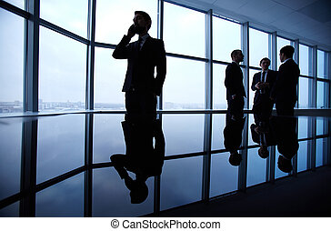 Office work - Group of colleagues standing against window in...