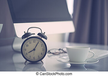 Office work space computer desk with coffe and clock, vintage colored filltered