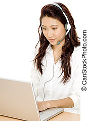 A young asian woman sitting at a laptop computer with a headset on
