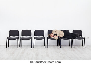 Office worker asleep on row of chairs - coping with overtime