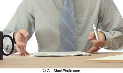 Office Worker Checks Papers - Office worker sitting at his...