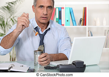 Office worker eating from tin can