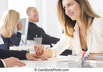 Office worker flirtatious touching co-workers hand