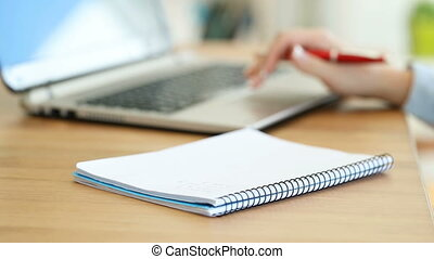 Office worker hand writing notes in a notebook on a desk -...