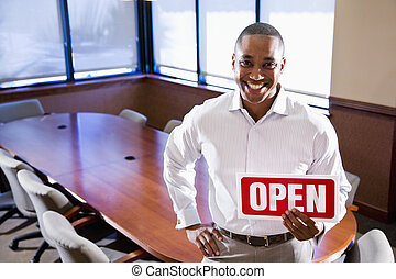 Office worker holding open sign in empty boardroom