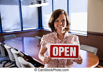 Office worker holding open sign in empty boardroom