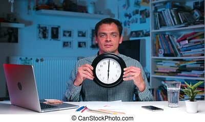 office worker holds the clock in his hands time on the clock 06:00