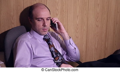 Office worker is talking on the mobile phone, he sits on the...
