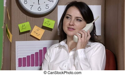 Office worker on the phone working in cardboard box