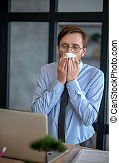 Dark-haired sick office worker sneezing all day