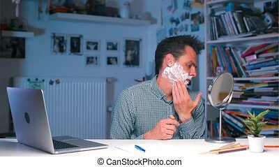 Office worker starts shaving at the table