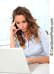 Office worker with desperate look in front of laptop