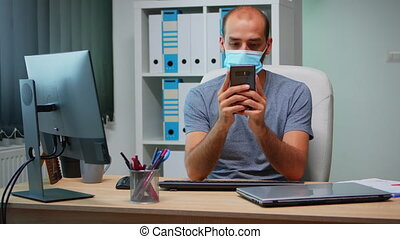 Office worker with protective mask using phone typing sitting on modern office during coronavirus. Freelancer working in new normal workplace chatting talking writing using mobile internet technology